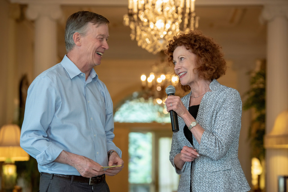 Former Colorado governor John Hickenlooper and Mary Snapp from Microsoft look at each other and smile. Mary has a microphone.